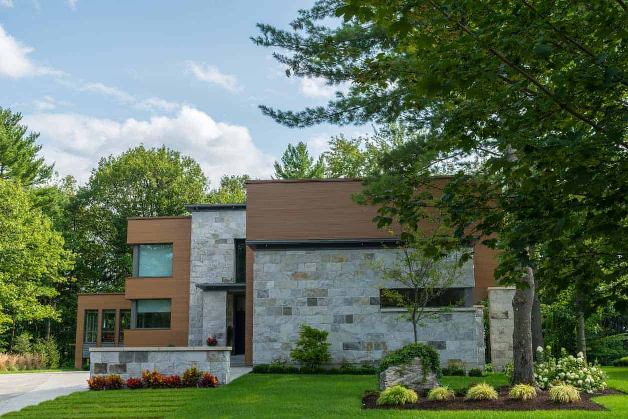 Here's a great example of a two story modern home with both wood and flagstone exterior in pretty much equal parts. It creates a dynamic curb appeal - the wood being smooth and uniform while the stone being rough, textured and colorful.
