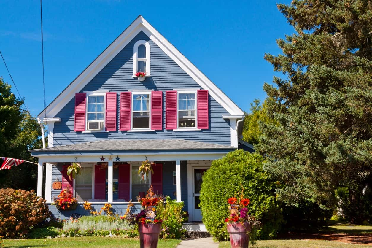 White trims outline this charming house while combining with the blue exterior for a classic look. The exterior siding add visual contrast that's caught on by the pink shutters which also add a touch of whimsy and character.