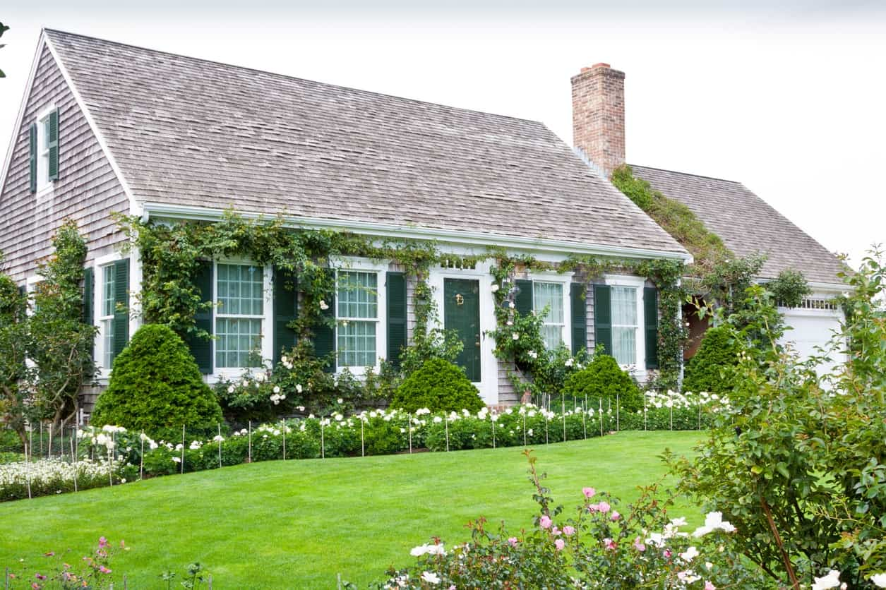 This ivy-covered house features shingles that run from the roof and down to the exterior siding as well as dark green shutters and doors and light green window sashes to intentionally blend with the green landscape. Crisp white trims create visual break and freshen up the overall look.
