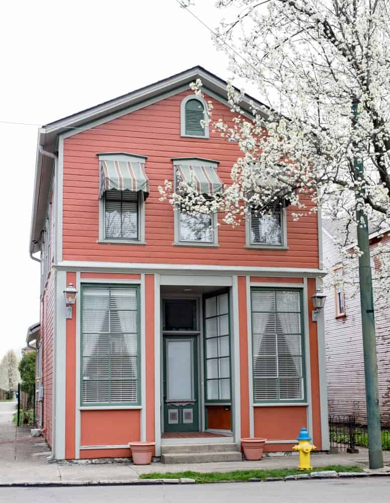 An off-white trim delineates this house's salmon exterior with green outlines on its front door and windows.