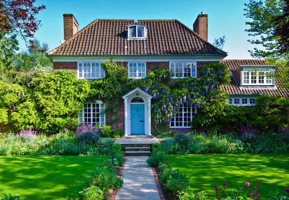 Brick suburban home with ivy growing around the white framed blue front door.