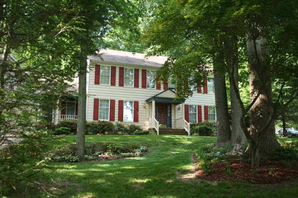 Bright red shutters adorn this white home nestled among huge trees on a large property. The red shutters are okay, but not my favorite. I prefer darker colors such as dark gray, black or dark blue.