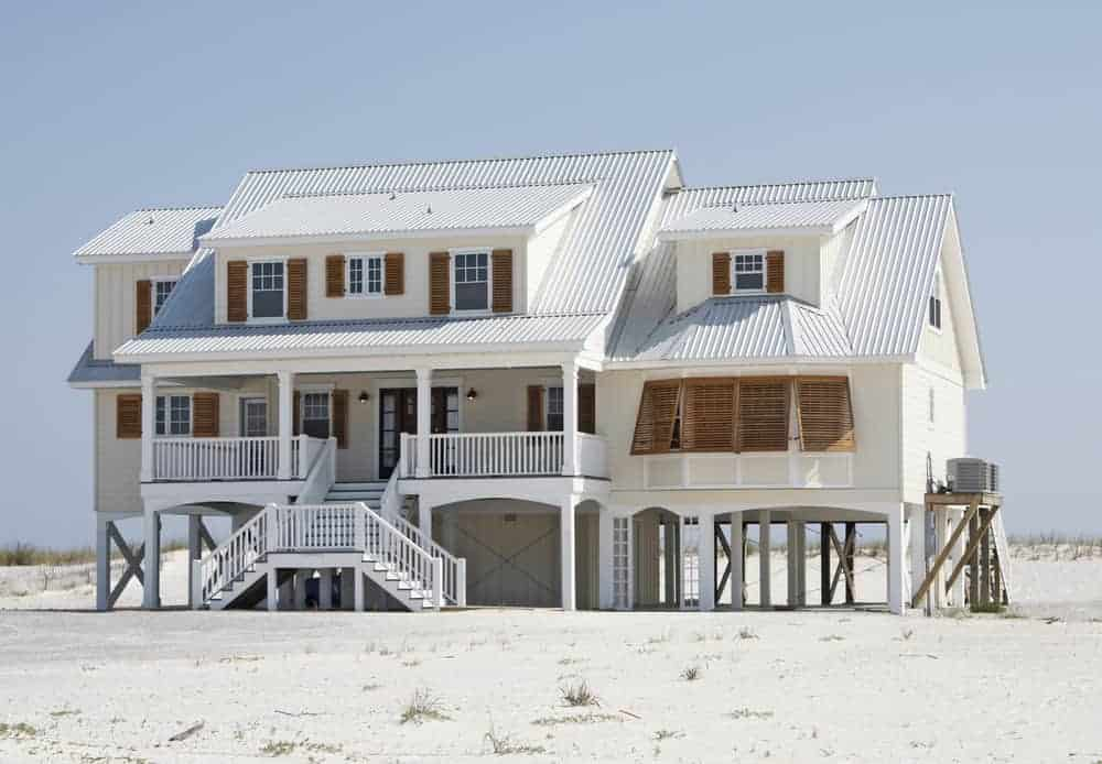 Here's an example of a beach house with shutters. These shutters are more functional than decorative... which is the case for most coastal homes. The shutters here are natural wood color; I think black or dark gray would be better. You really can't get more a beach house than this.