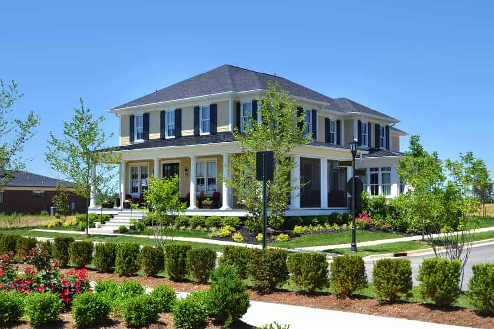 Here's a large beige exterior home with black shutters on the upper floor. There are many windows on this house and so the shutters really stick out. I love the look... picture the home without shutters; it simply wouldn't look the same.