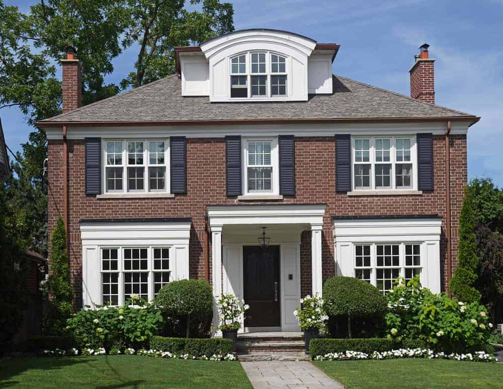 Another red brick exterior home with louvered black shutters on the upper floor windows only.