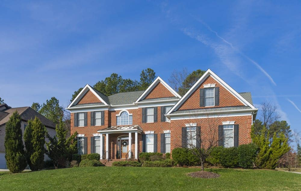 Contemporary McMansion red brick exterior home with dark gray shutters. It works fine. I know McMansions get knocked a lot, but I don't mind some of them. This is a nice enough house where the shutters work just fine.