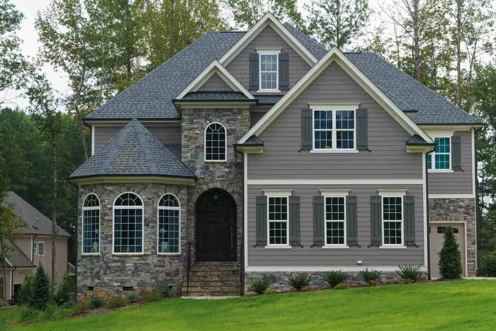 Great example of blending exterior shutters with the home exterior. The shutters are a smidgen darker the exterior. I like this look a lot.