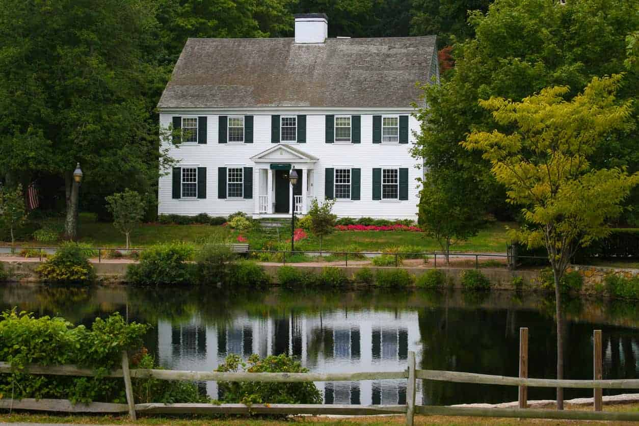 Historic (1693) New England Home with white clapboard exterior, grey shingle roof and black window shutters in Sandwich, Cape Cod, Massachusetts. Talk about picturesque.