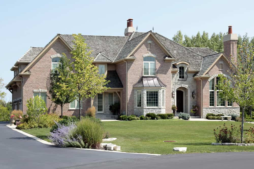 A fancy stone house with a spacious built Its unique windows highlight the overall appearance of the house. It has a big custom-shaped window on the right side and an elegant-looking bay window at the central part of the mansion.