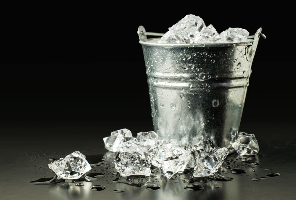 A stainless steel bucket containing cubes of ice.