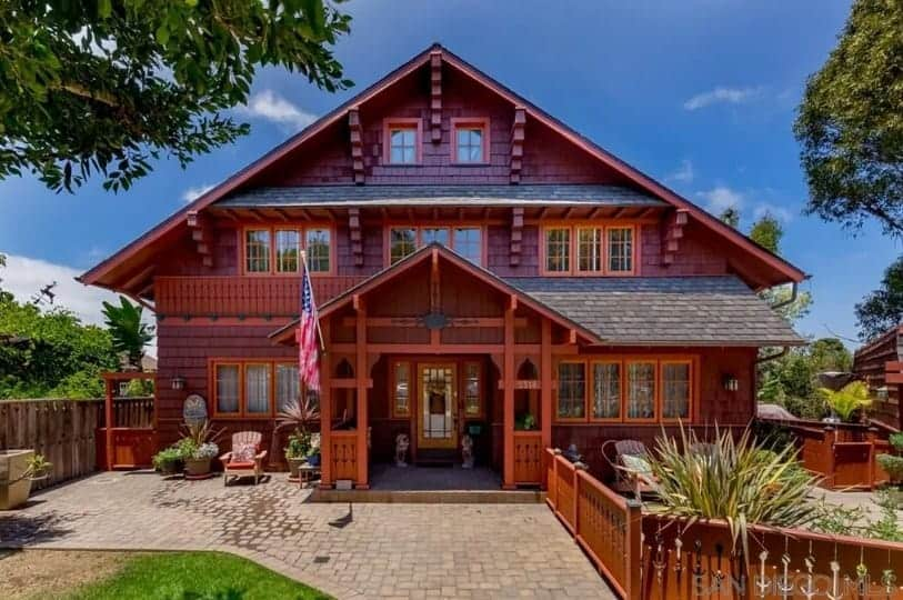 A rustic wooden house that is restored to its former beauty. It has a nice front yard with a garden and a lawn area as well.