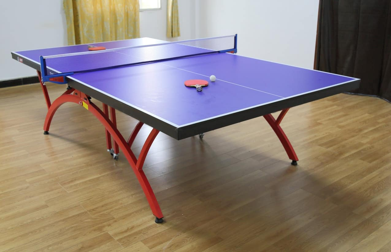 Blue indoor ping-pong table with red curved legs standing on wood flooring.