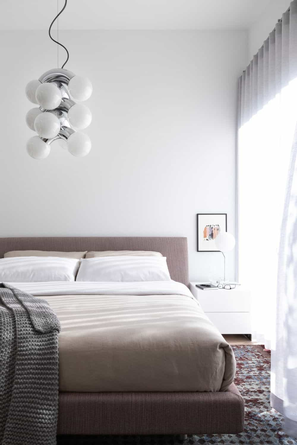 Another bedroom features a queen size bed lighted by a stylish ceiling light. Photo credit: Ema Peter