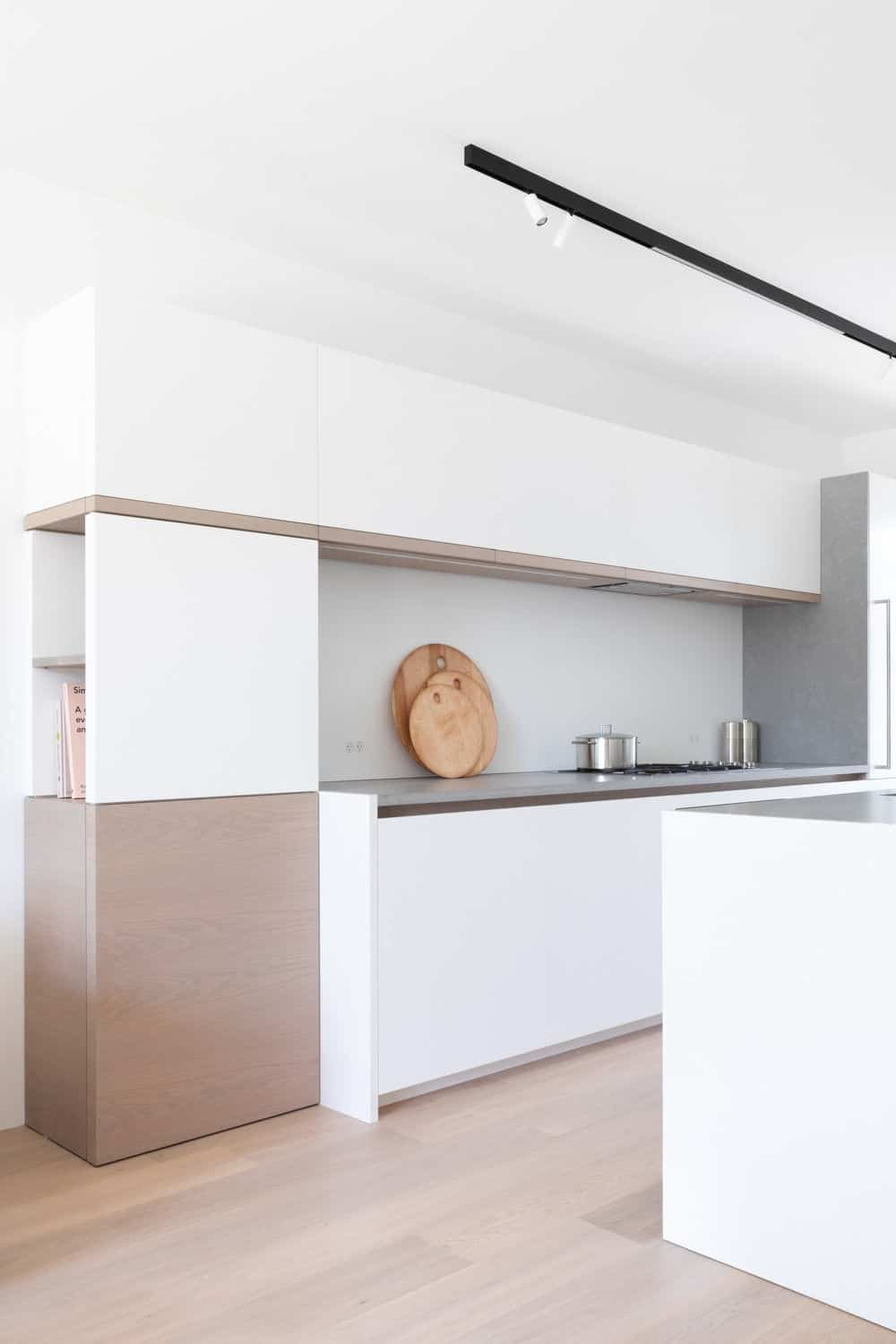 Another view of the kitchen featuring its white walls, smooth counters and white walls. Photo credit: Ema Peter
