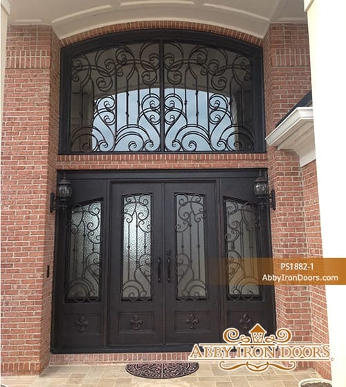 Large and wide wrought iron door on brick walls.