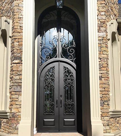 Tall wrought iron door on a well-finished walls and has a pendant lamp on top.