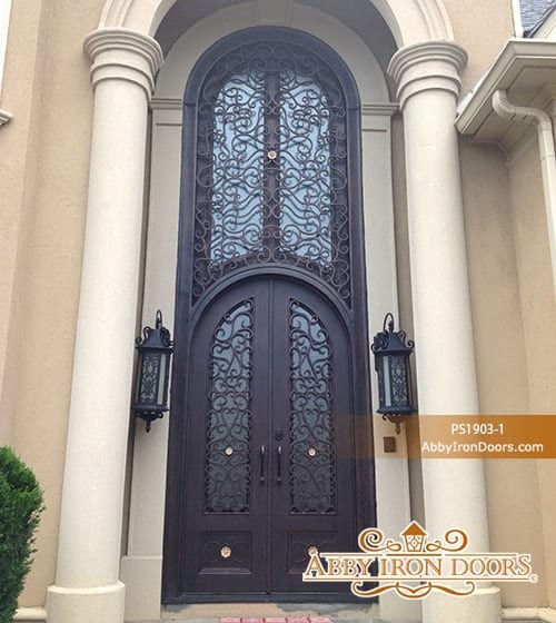 Tall wrought iron door with a couple of wall lamps on both sides.