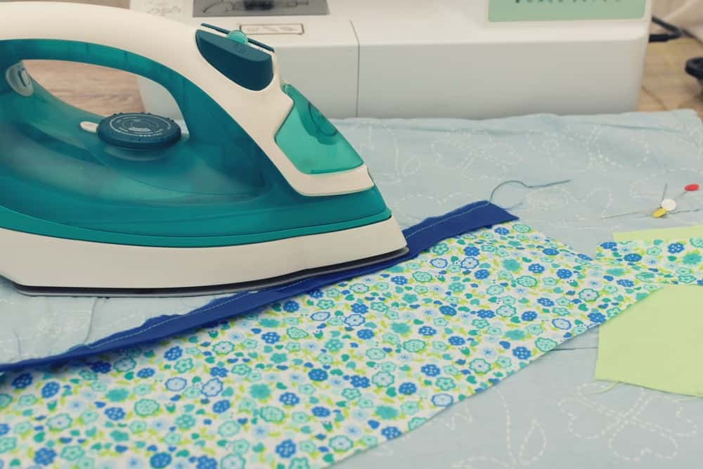A green iron is being used to iron out a piece of fabric.