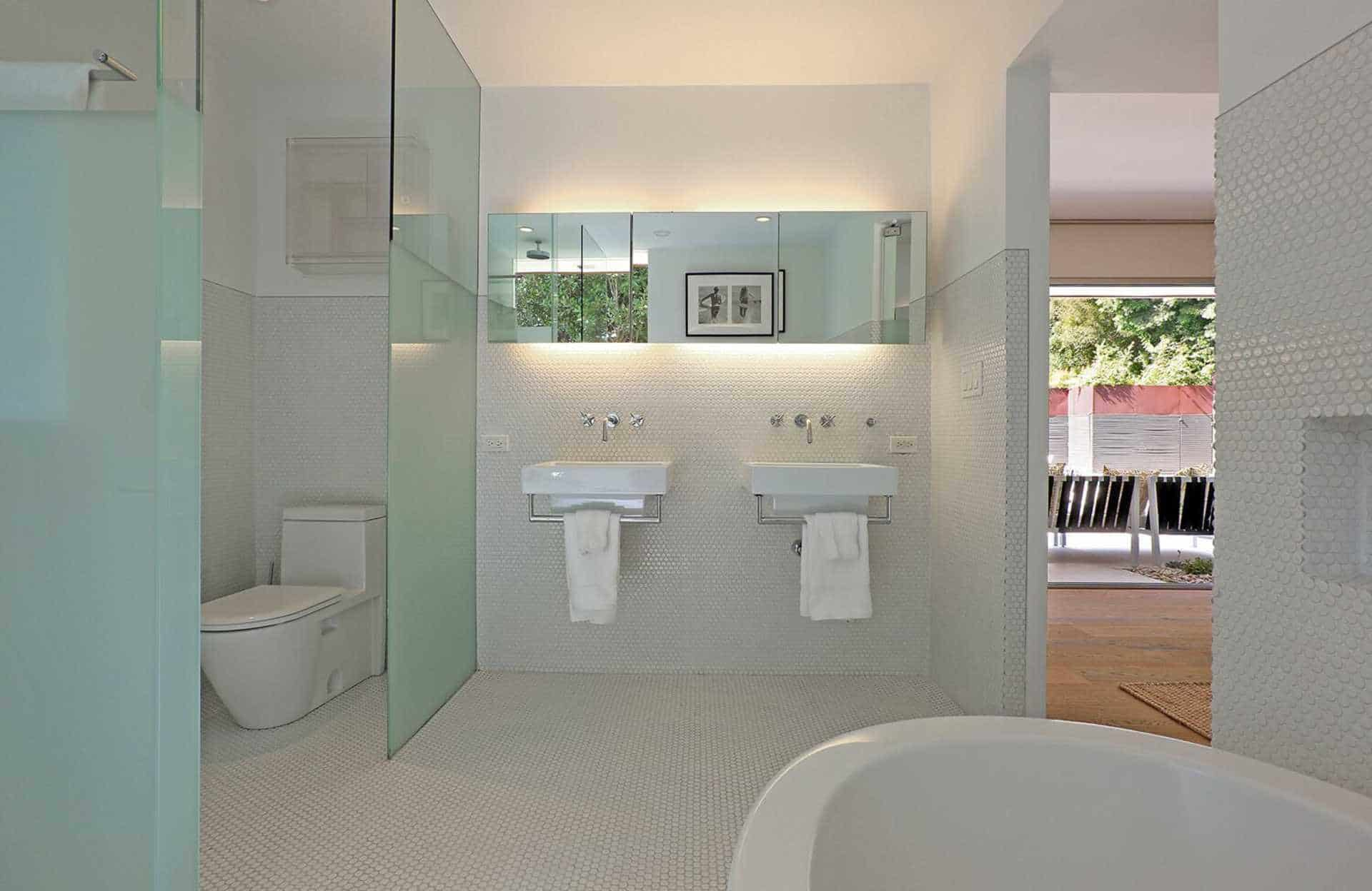 This primary bathroom in mid-century style features tiles flooring and walls, along with two floating sinks and a freestanding tub.
