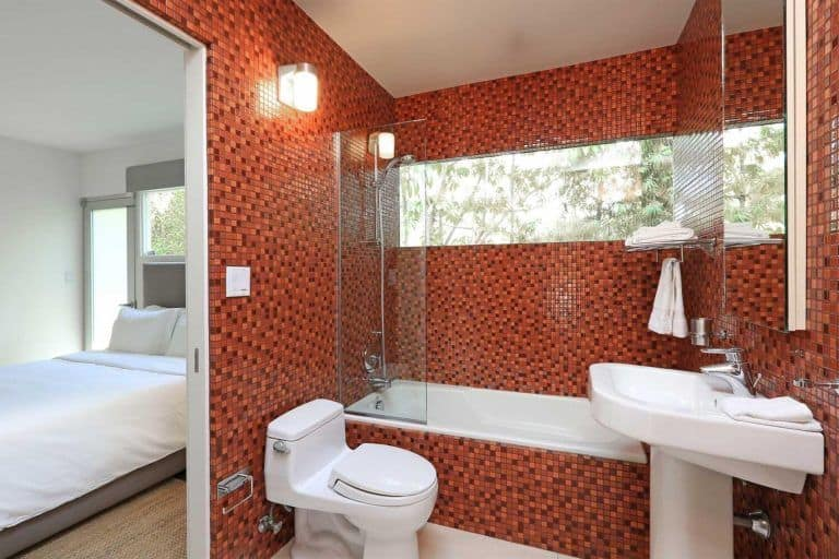 The bathroom features red tiles walls, bathtub and shower combo along with toilet and sink.