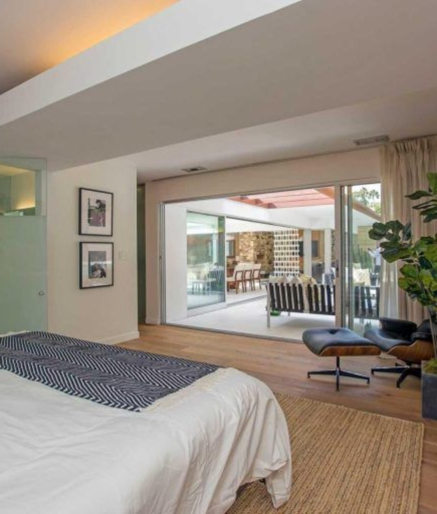 The bedroom features large bed and stylish wall decors along with a doorway leading to outdoor amenities.