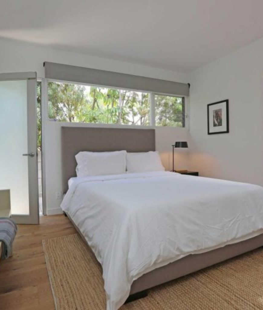 Another bedroom featuring a large bed along with a couch on the side. The room also has its own stylish bathroom.