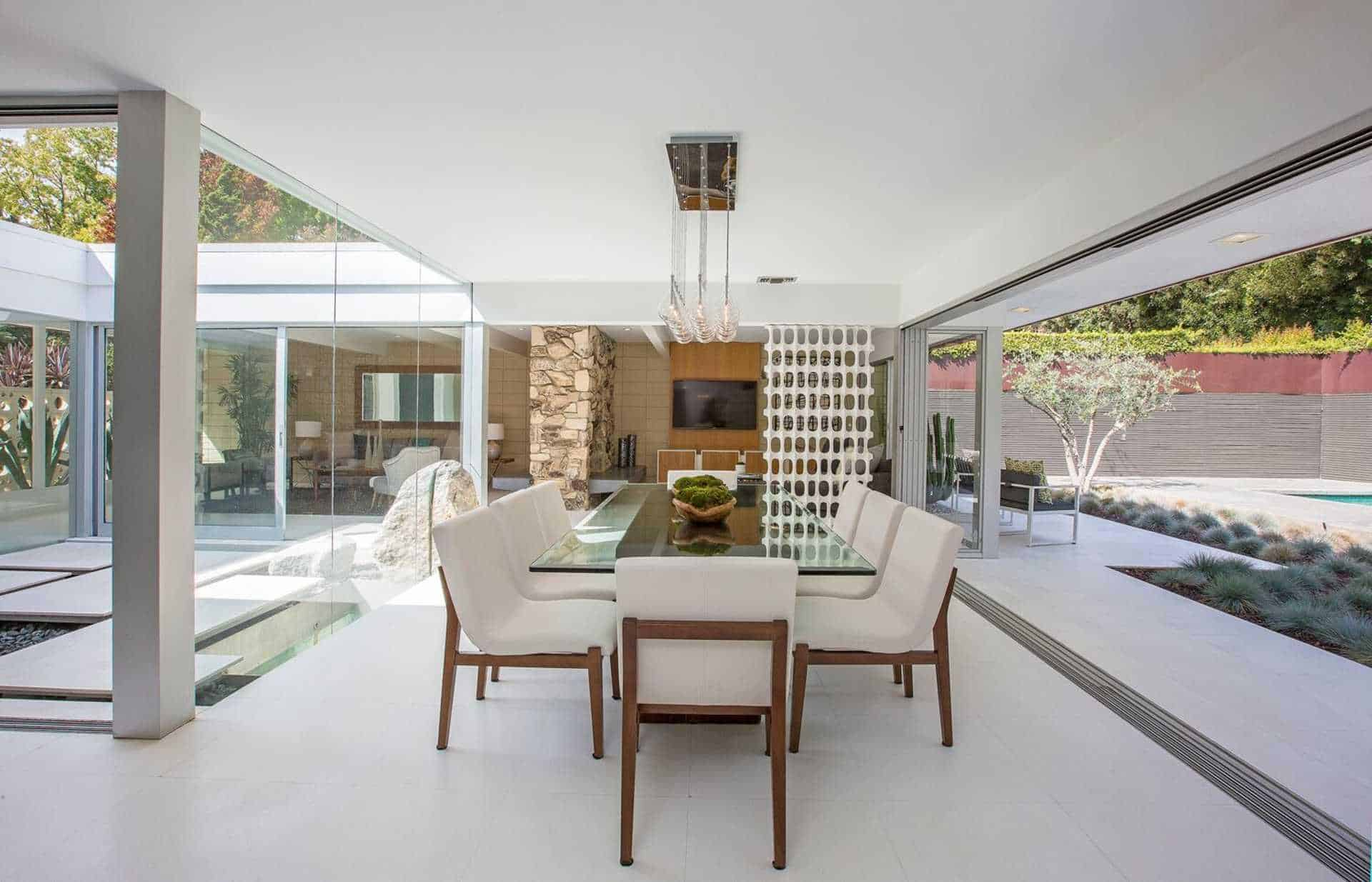 The dining room offers a glass table with modern seats surrounded by glass sliding door and walls.