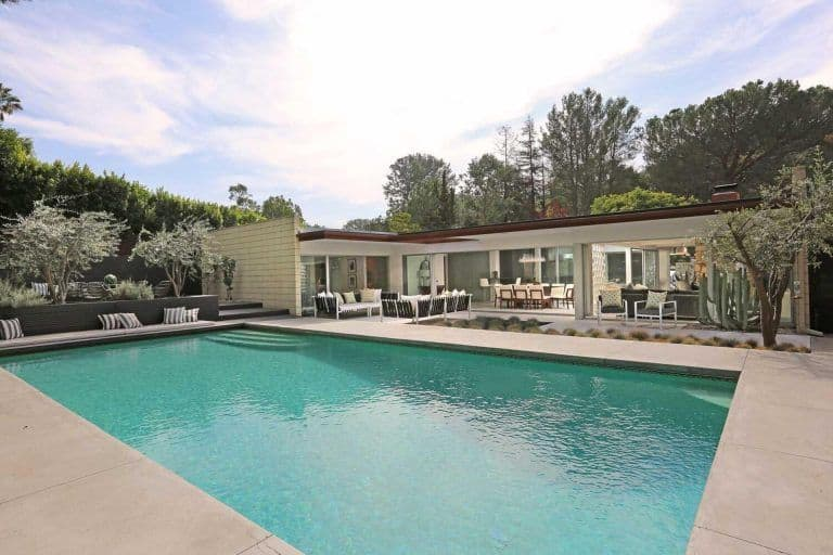 The rectangular swimming pool mirrors the Hollywood Hills skies and is surrounded by beautiful landscaping trees.