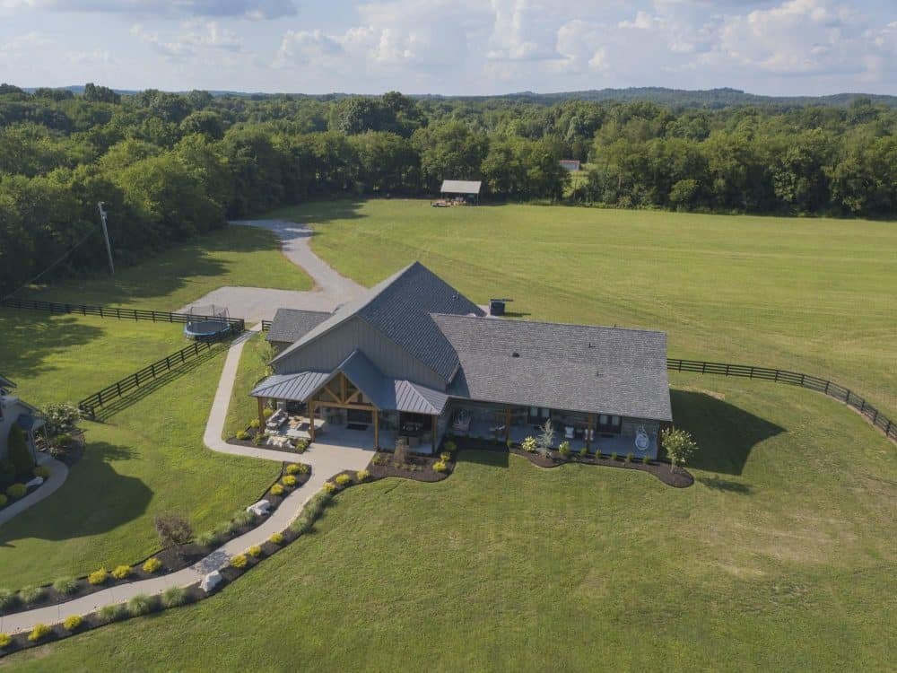 Aerial view of the property showcasing the vast open field surrounded by healthy mature trees.