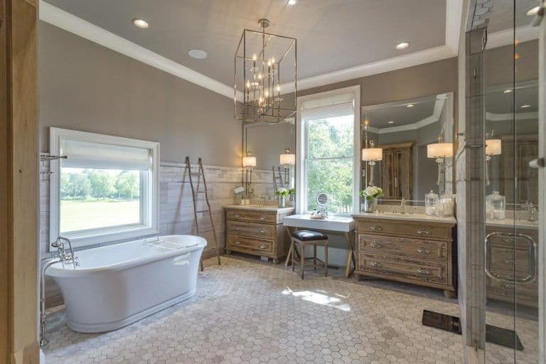 A rustic primary bathroom illuminated by a caged chandelier and sconces mounted on the frameless mirrors that are attached to the wooden sink vanities. It has a walk-in shower and a freestanding tub over hex tiled flooring.