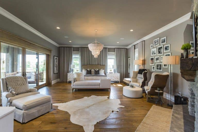 Gray primary bedroom designed with gallery wall along with a white chandelier and beige cowhide rug that lays on natural wood plank flooring.