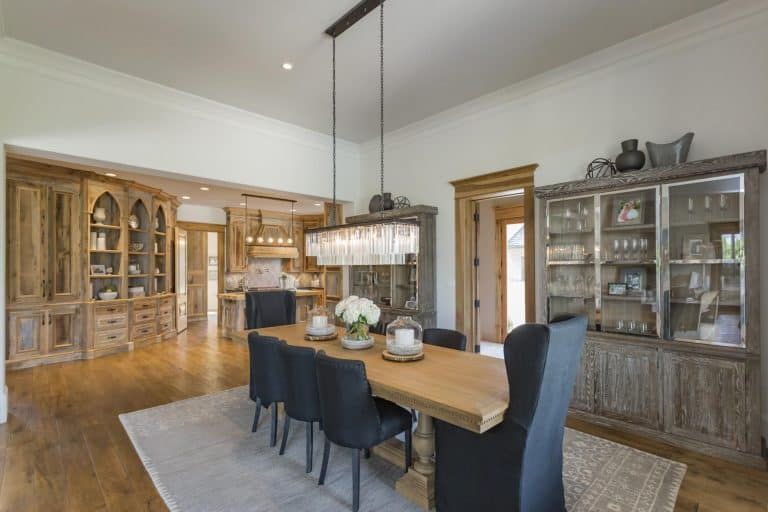 An elegant linear chandelier hangs over the wooden dining table that's paired with black cushioned chairs in this dining room with rustic cabinets and gray area rug.