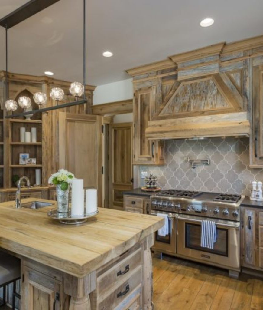 The kitchen's old rustic style looks beautiful with its appliances and lighting.