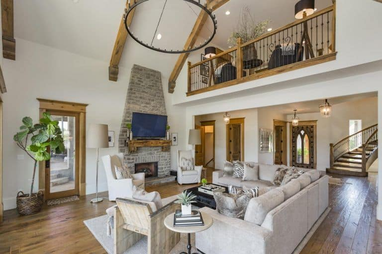 White wingback chairs sit in front of the stone fireplace that's lined with a wooden mantel below the television in this living room with vaulted ceiling and wood plank flooring.