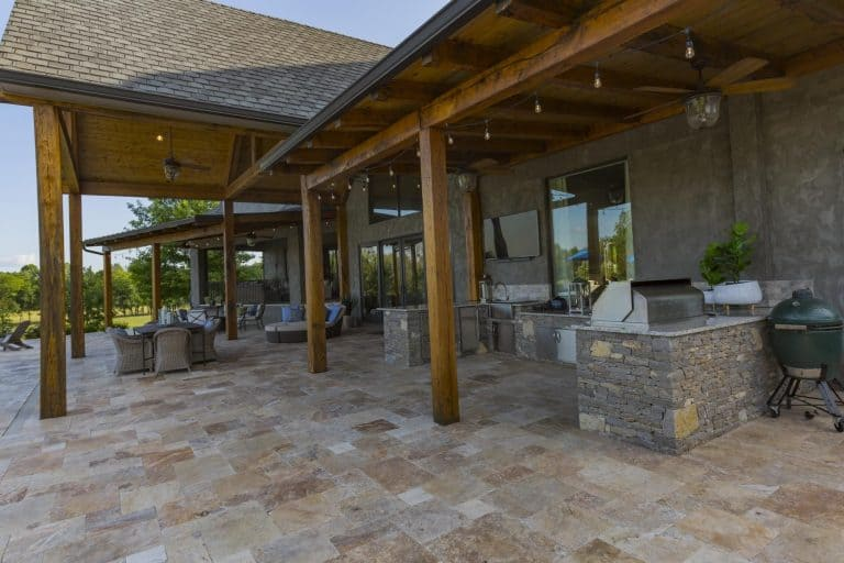 The outdoor kitchen features brick ground that extends to the patio area.