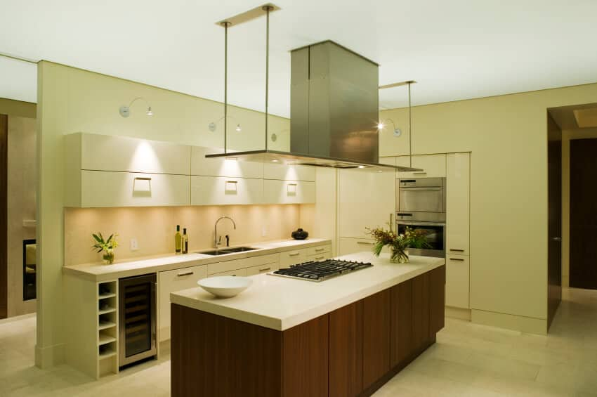 Sleek, modernist kitchen replete with glossy white paneling throughout, with natural wood island with built-in range.