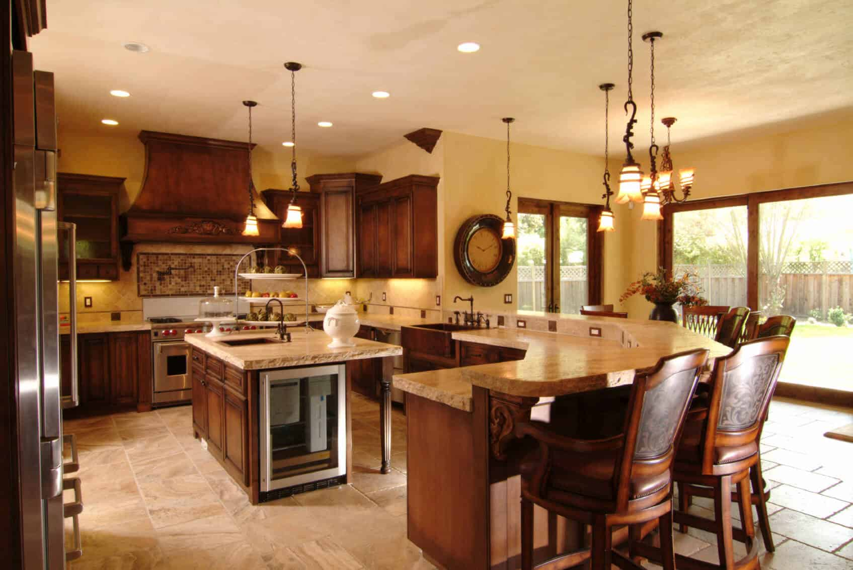 In this kitchen defined by wraparound counter space, modest sized island commands attention with built-in wine cooler and full sink over dark hardwood paneling.