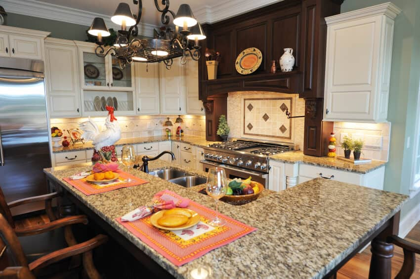 Compact, richly detailed kitchen holds this two-tiered island with built-in sink and raised dining surface.