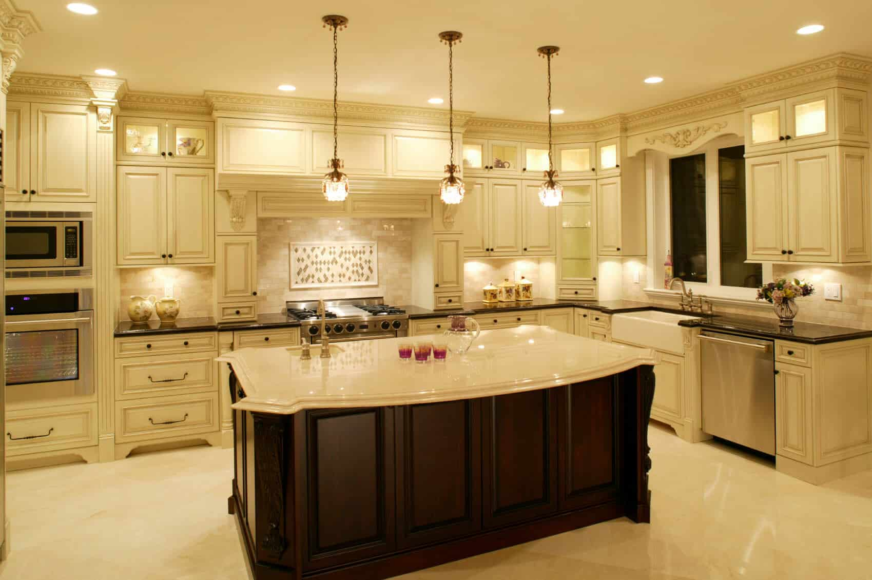 Luxurious kitchen awash in light marble tones, dominated by large dark wood island with filigreed siding and built-in secondary sink.