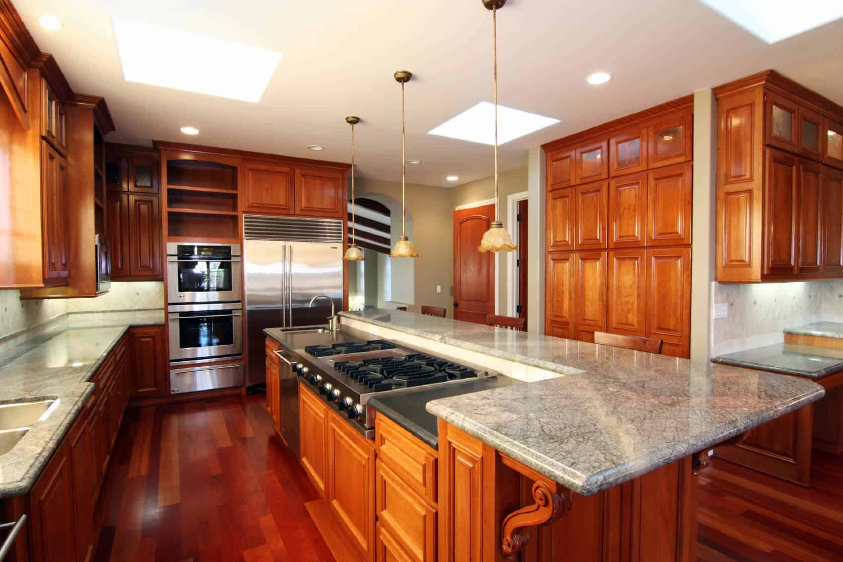 Kitchen centered around lengthy island featuring full range, sink, and dishwasher, plus raised marble countertop for dining.