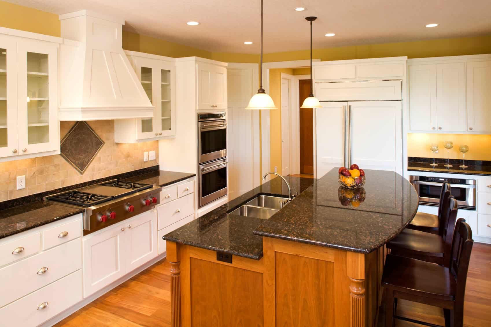 Here we have another two-tiered island adding contrast to a kitchen with warm natural wood and dark marble countertop.  Compared to others in this gallery, this is an example of a smaller kitchen island.