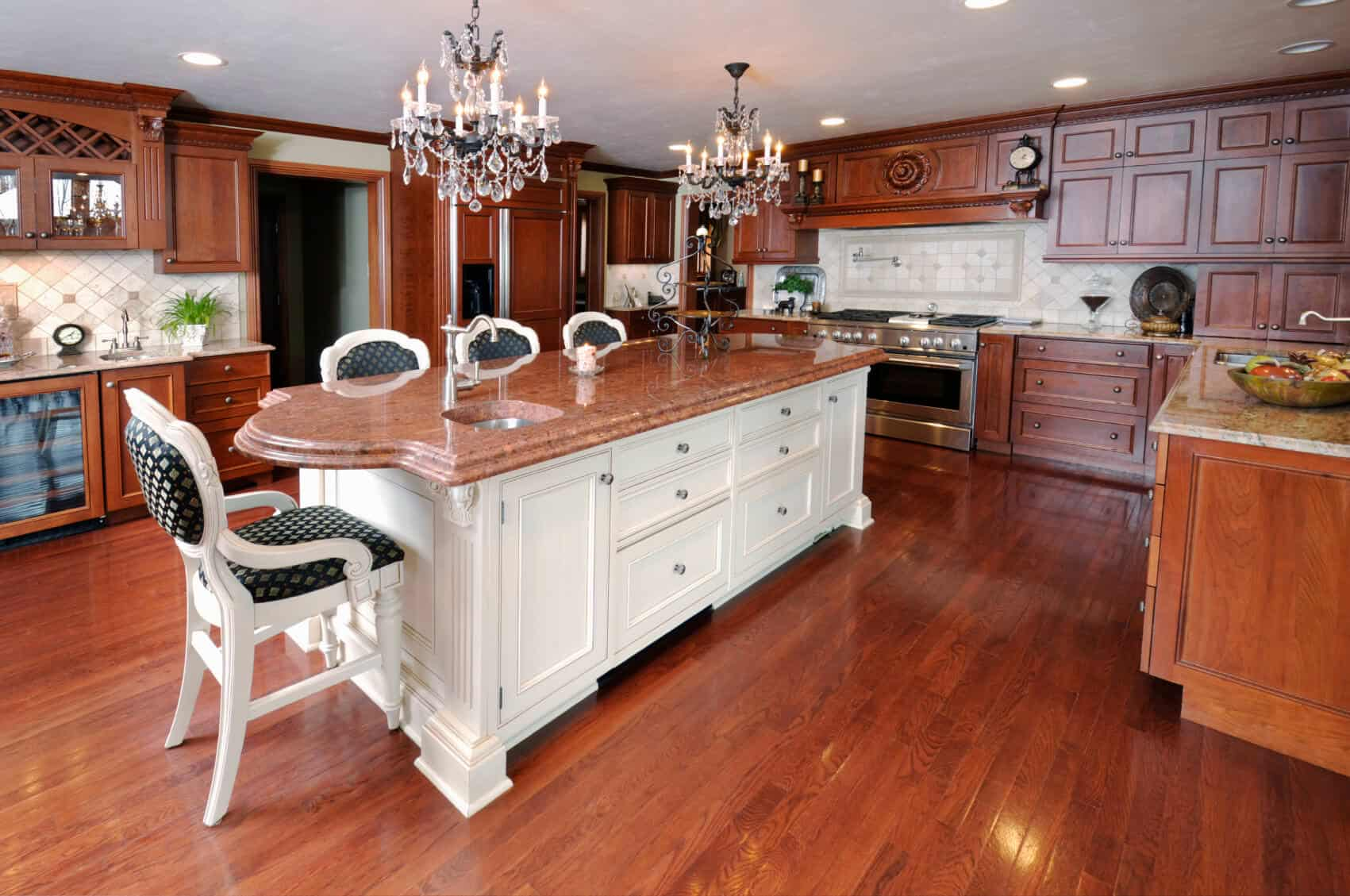White island with rosy marble countertop under dual chandeliers stands apart in this natural wood toned kitchen.