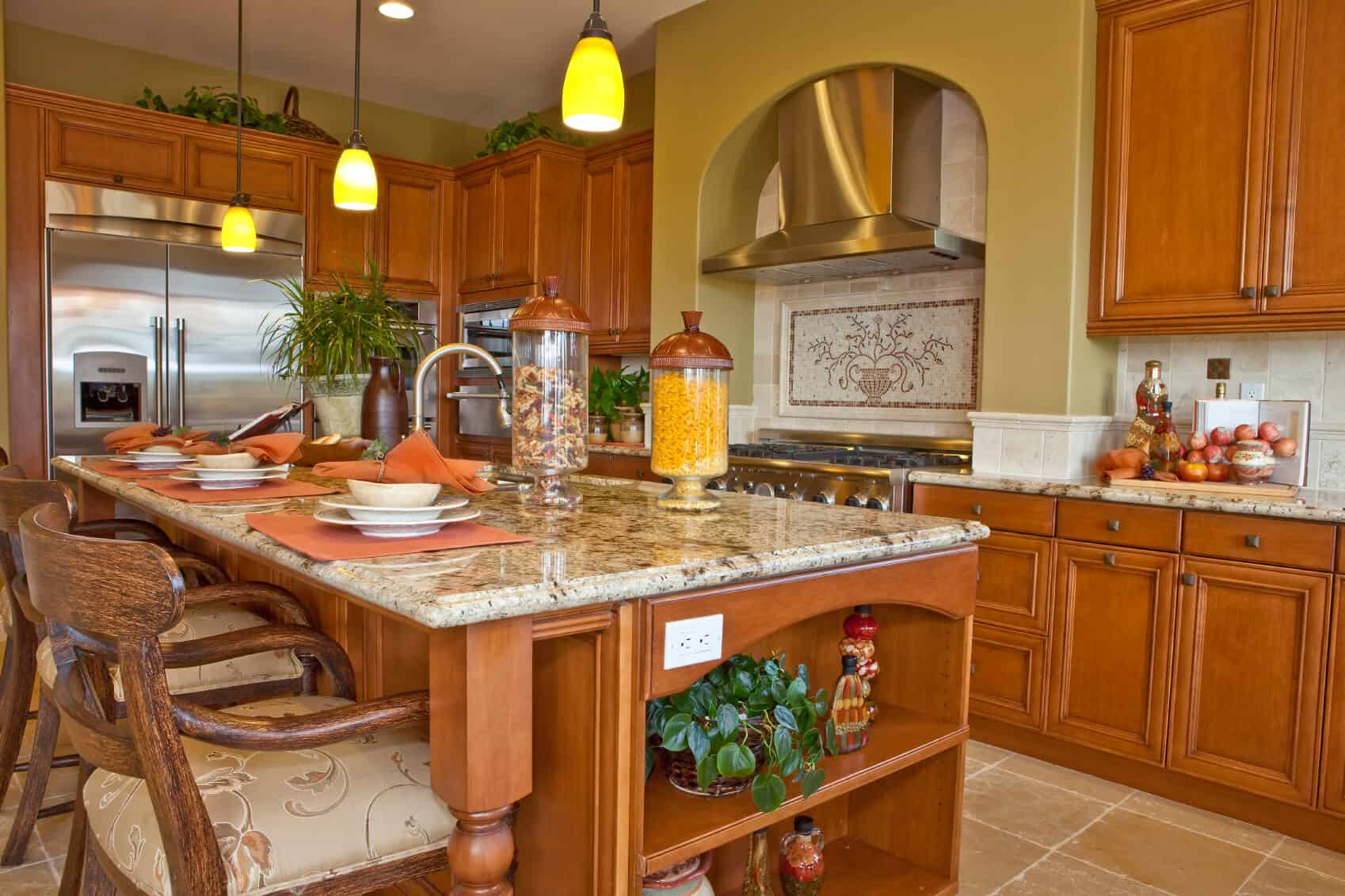 Warm wood tones unify this kitchen featuring large island with ample seating area, built-in shelving and full kitchen sink.