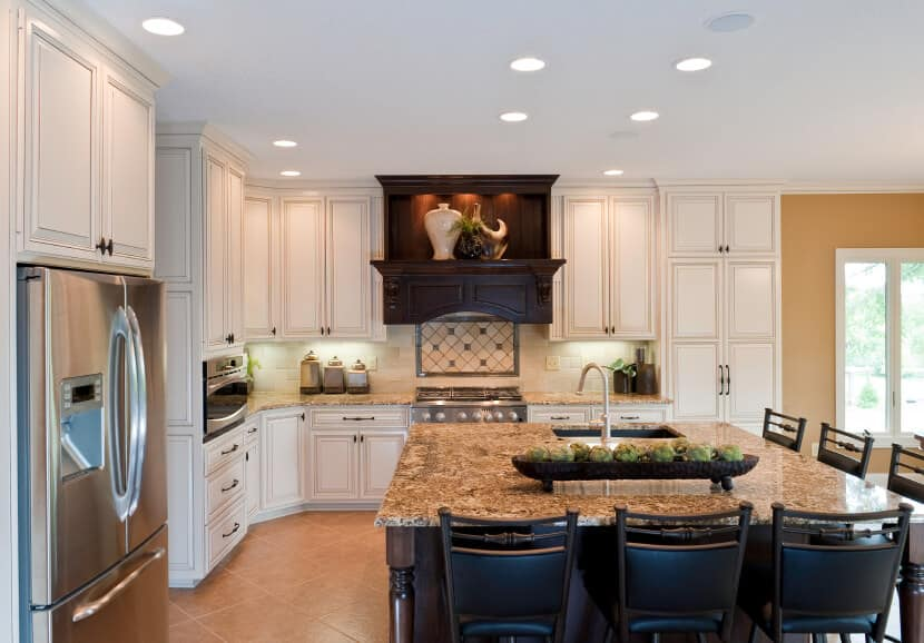 Dark wood and marble countertop island stands out in this white and beige kitchen, with ample dining seating all around.  This is a great example of a natural wood kitchen in an otherwise white kitchen.