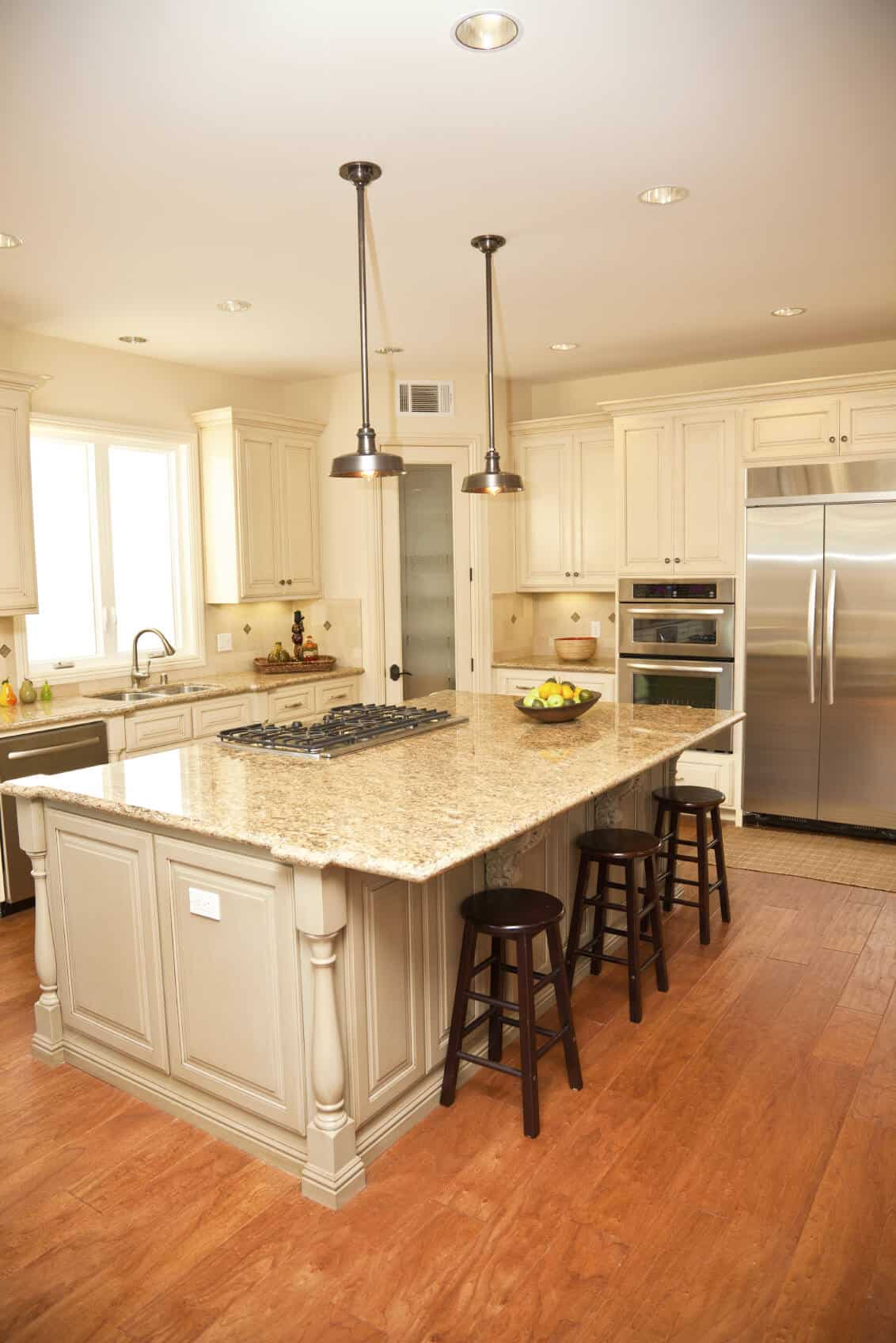 Kitchen island photo of a luxurious beige tone island features wide overhang for dining, with built in range.