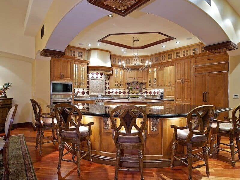 Truly ornate wraparound island features under-counter lighting and expanse of black marble countertop, with seating for 5.