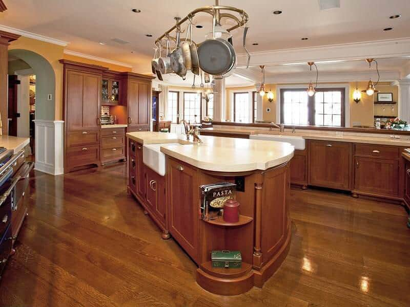 Wide open space centered around oblong island in natural wood cabinetry, topped with white marble under large metal pot hanger.