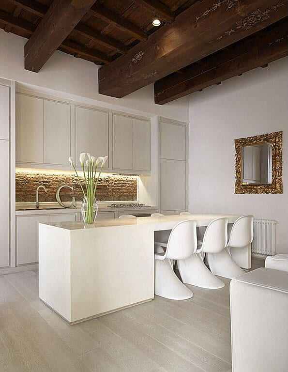 All-white kitchen replete with minimalist wood island and dining table hybrid. Large natural wood beams above add contrast.