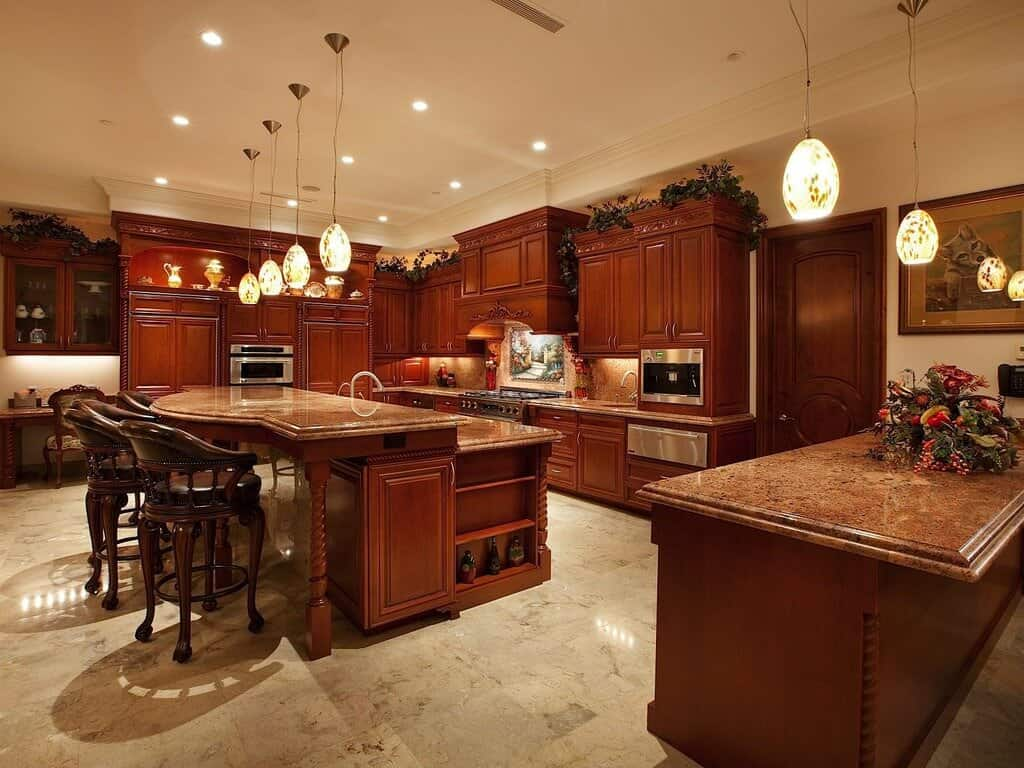 Rich red wood over beige marble flooring throughout this kitchen. Large two-tiered island with marble countertop features dining seating and built-in storage.