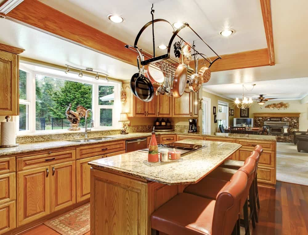 Open concept kitchen with hanging pot rack, tray ceiling, recessed lighting, and an island breakfast bar.